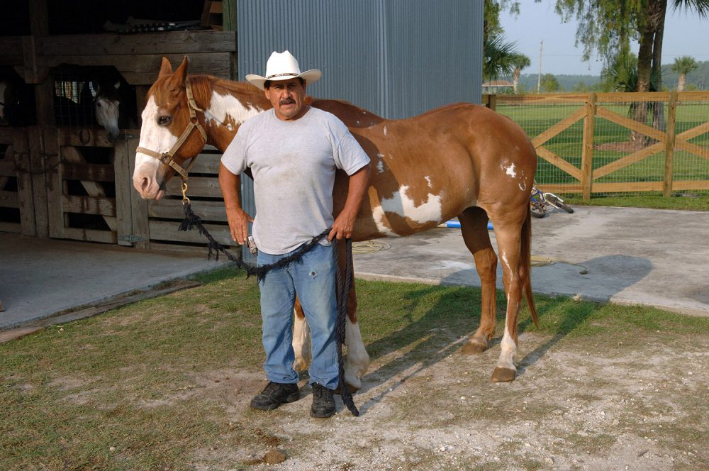 A ranch hand holding the lead line for a horse that is standing behind him